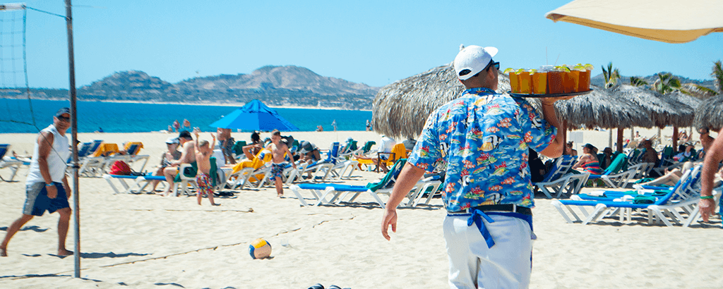 Waiter delivering drink at the Beach of Royal Solaris Los Cabos